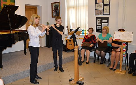 Žena a chlapec hrají na příčnou flétnu